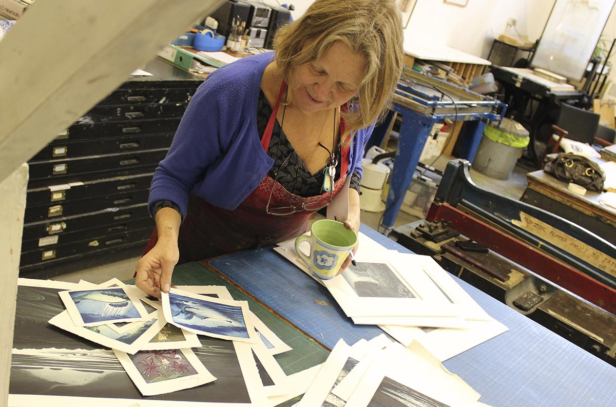 Morna Rhys looking over her prints